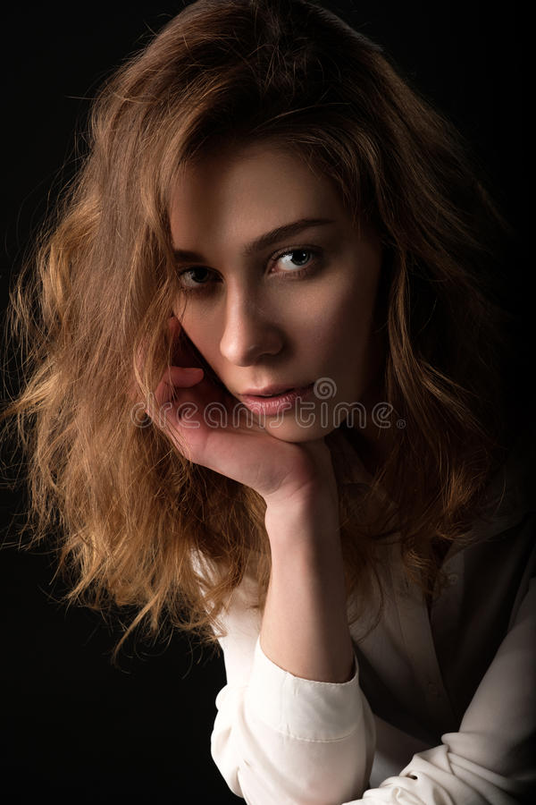 Sluit omhoog studioportret van jonge ernstige vrouw in witte blouse op zwarte achtergrond stock afbeeldingen