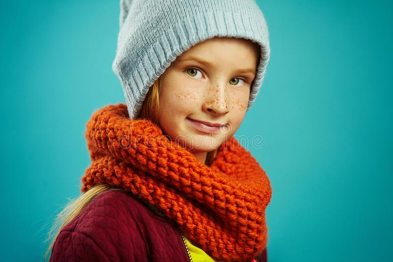 Sluit omhoog studioportret van mooi kindmeisje die een ronde hoed van de sjaal oranje en blauwe winter dragen Seizoengebonden Ass royalty-vrije stock afbeelding