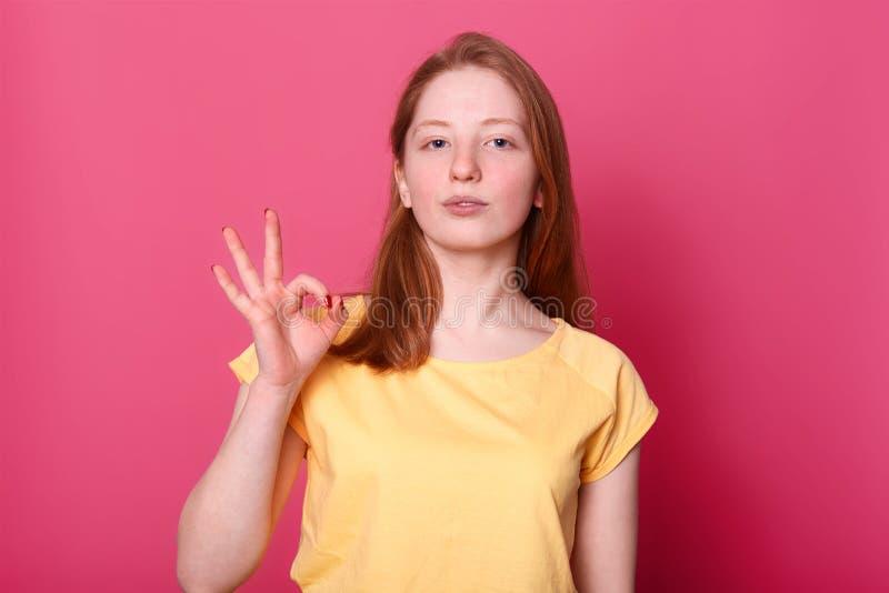 Sluit omhoog studioportret van rode haired jonge meisje stevig status, tonend o.k. teken, kijkt ernstig en zeker Weinig charmeren stock foto