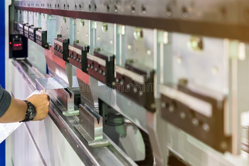 Sluit omhoog tanden van semi automatische buigende machine en hand van het metaalblad van de mensengreep tijdens het werken royalty-vrije stock foto's