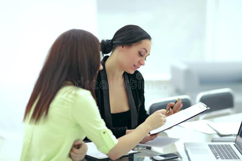 Sluit omhoog twee bedrijfsvrouwen die financi?le documenten bespreken stock afbeelding