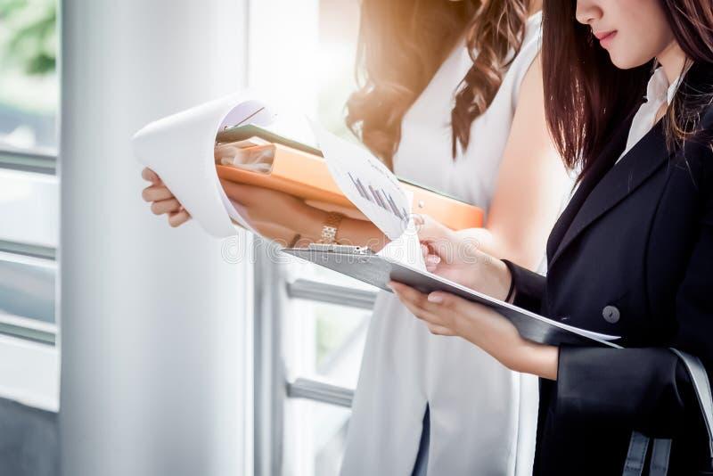 Sluit omhoog twee jonge onderneemsters die de omslag van het documentdossier voor daarna het analyseren van winstomloop of verkoo royalty-vrije stock foto's