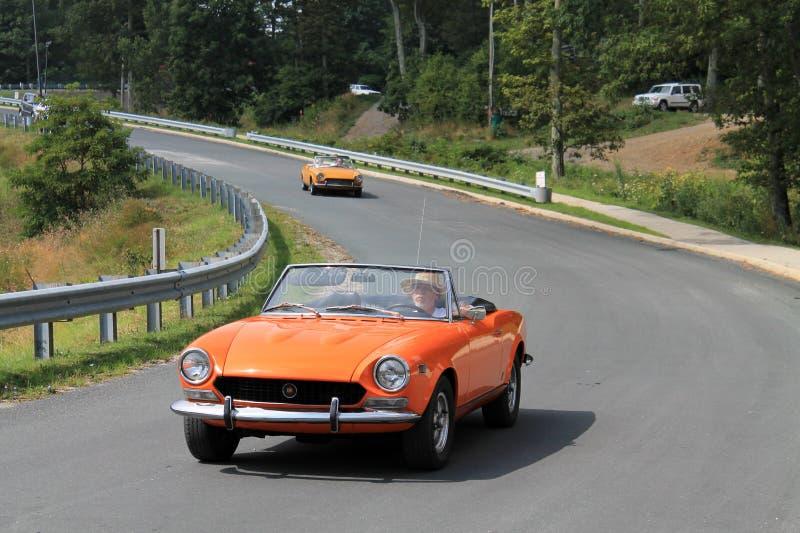 Sluit omhoog Twee klassieke oranje Italiaanse sportwagens op weg stock fotografie