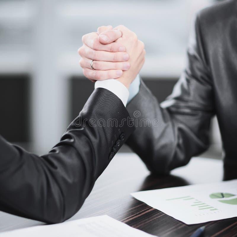 Sluit omhoog twee zakenlieden zijn bezig geweest met wapen worstelend bij een Bureau royalty-vrije stock foto