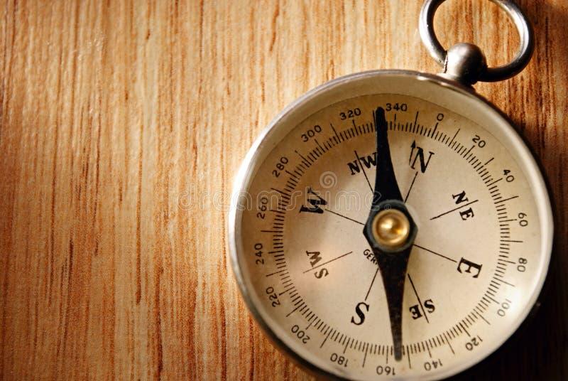 Sluit omhoog Uitstekend Kompas die op Houten Lijst liggen stock fotografie
