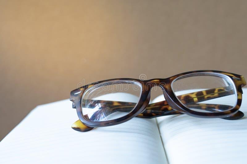 Sluit omhoog uitstekende glazen op vaag geopend boek met exemplaarruimte stock afbeeldingen