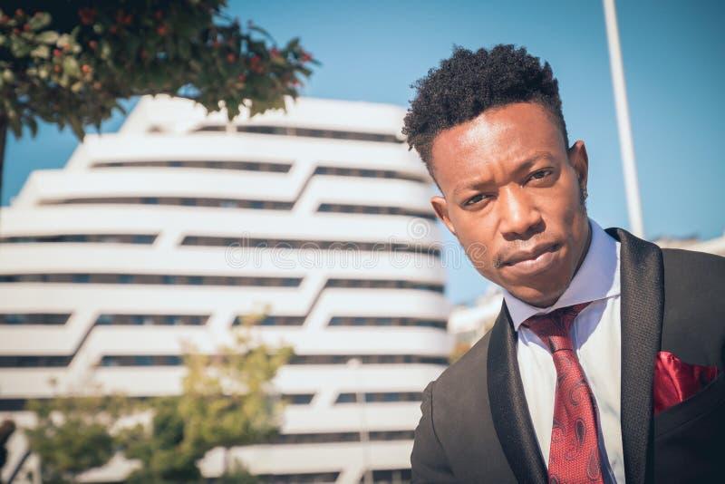 Sluit omhoog van één jonge en aantrekkelijke zwarte zakenman die de camera voor een modern gebouw in de stad bekijken die B drage stock afbeeldingen