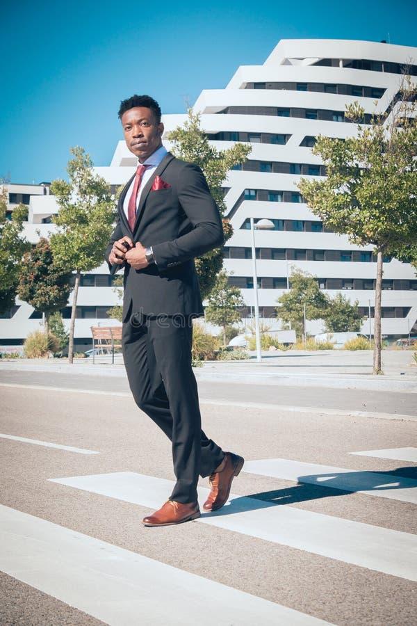 Sluit omhoog van één jonge en aantrekkelijke zwarte zakenman die door een voetgangersoversteekplaats gaan en telefonisch voor a s stock foto's