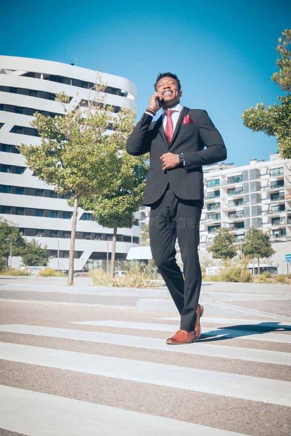 Sluit omhoog van één jonge en aantrekkelijke zwarte zakenman die door een voetgangersoversteekplaats gaan en telefonisch voor a s stock foto