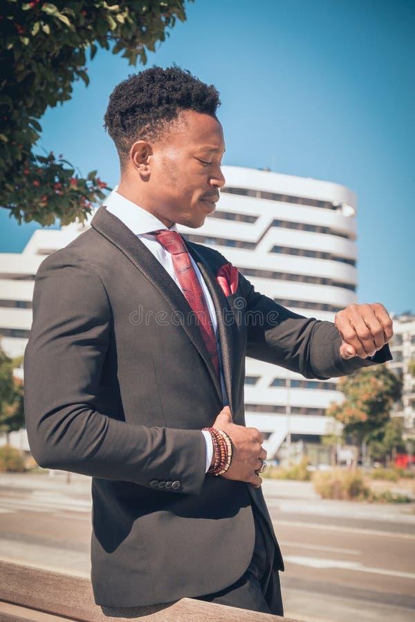 Sluit omhoog van één jonge en aantrekkelijke zwarte zakenman die door een voetgangersoversteekplaats gaan en telefonisch voor a s stock afbeelding