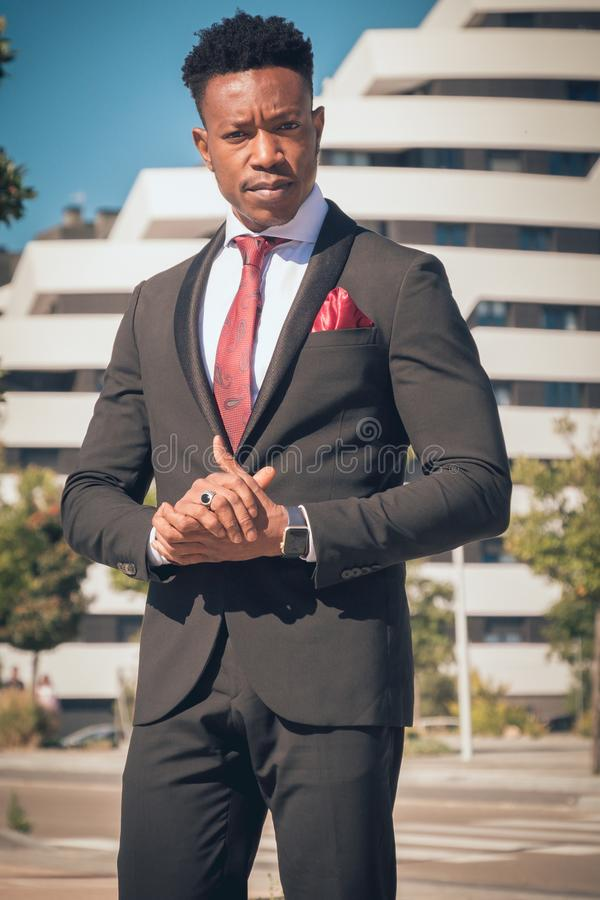 Sluit omhoog van één jonge en aantrekkelijke zwarte zakenman die door een voetgangersoversteekplaats gaan en telefonisch voor a s royalty-vrije stock afbeelding
