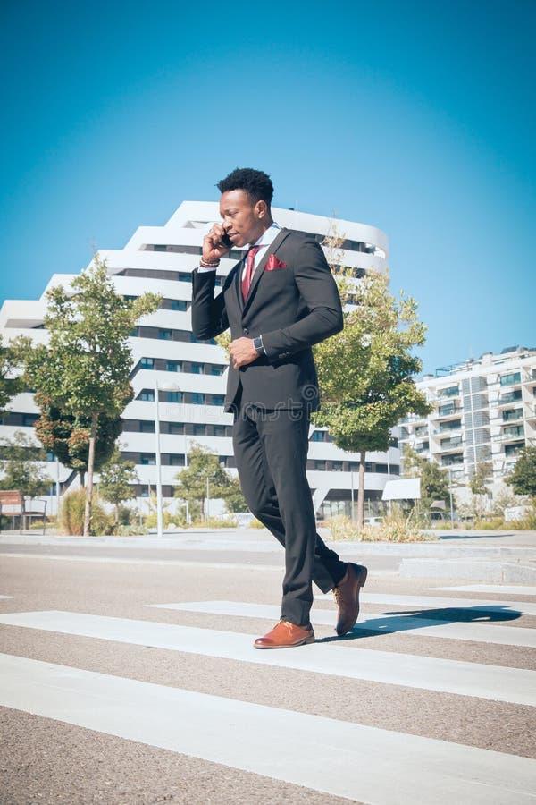 Sluit omhoog van één jonge en aantrekkelijke zwarte zakenman die door een voetgangersoversteekplaats gaan en telefonisch voor a s royalty-vrije stock foto