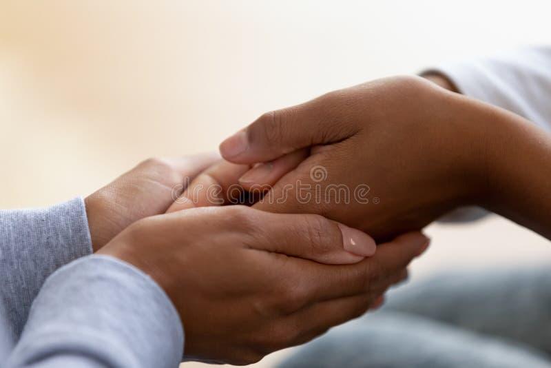 Sluit omhoog van Afrikaanse Amerikaanse het geven het kindhanden van de mammaholding royalty-vrije stock afbeeldingen