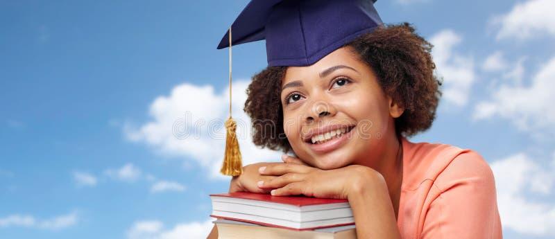 Sluit omhoog van Afrikaanse gediplomeerde student met boeken royalty-vrije stock afbeelding