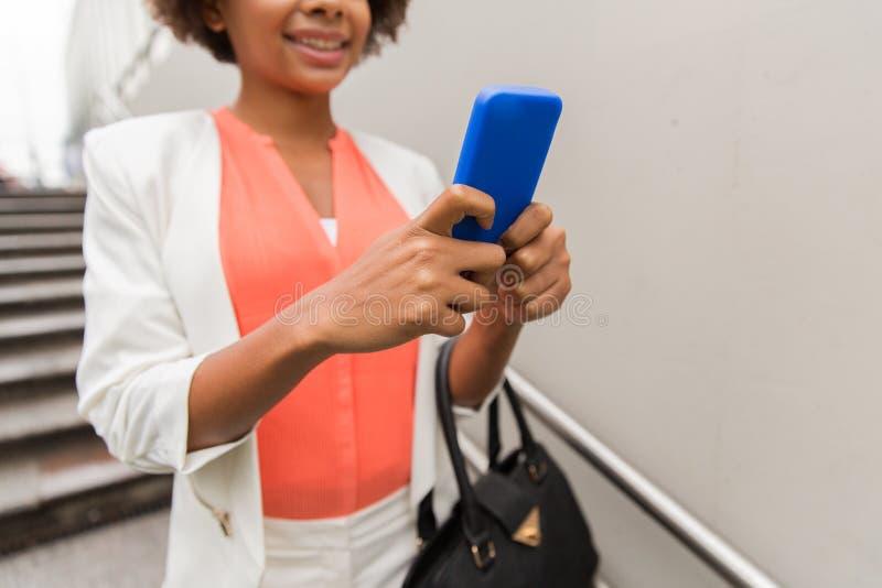 Sluit omhoog van Afrikaanse vrouw met smartphone in stad stock afbeeldingen