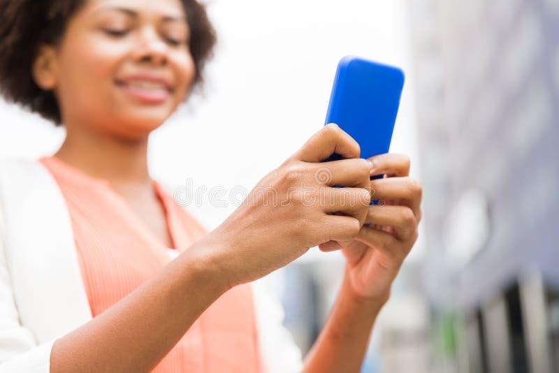 Sluit omhoog van Afrikaanse vrouw met smartphone in stad royalty-vrije stock afbeeldingen