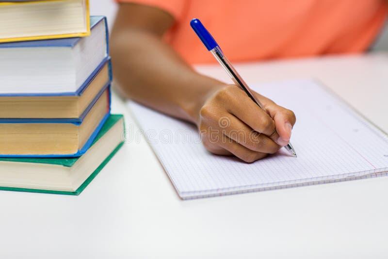 Sluit omhoog van Afrikaanse vrouwenhand schrijvend aan notitieboekje royalty-vrije stock afbeeldingen