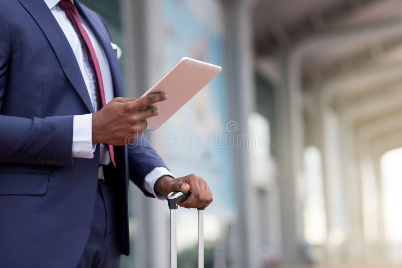 Sluit omhoog van Afrikaanse zakenman die een tablet en een koffer in luchthaven houden royalty-vrije stock fotografie