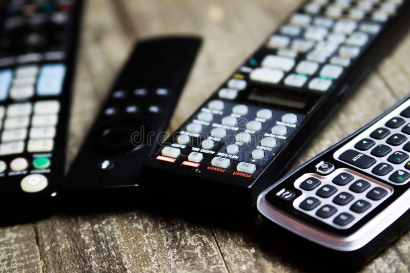 Sluit omhoog van afstandsbedieningen voor Video en stereomuzieksysteem het van TV, op houten lijst royalty-vrije stock afbeeldingen