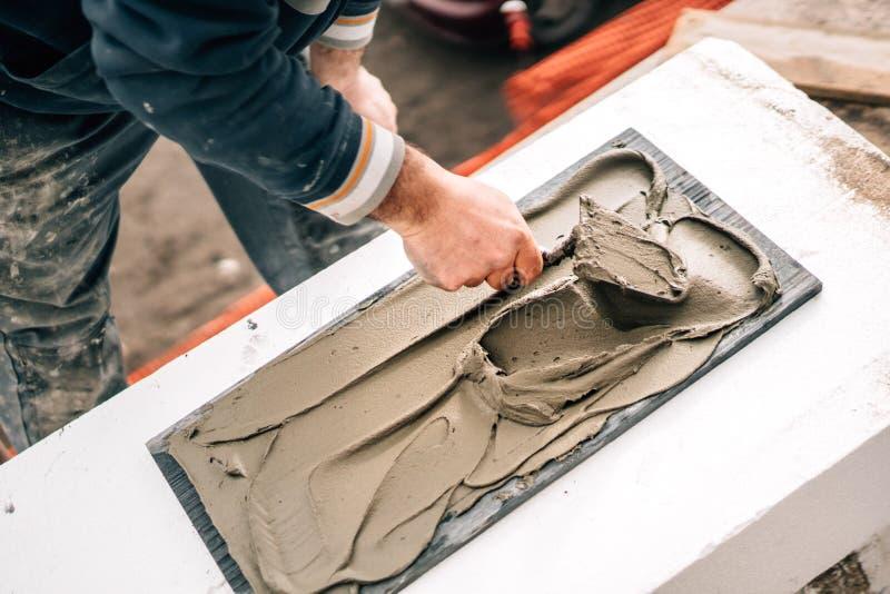 Sluit omhoog van arbeider het werken met steen, toevoegend kleefstof met troffel stock foto's