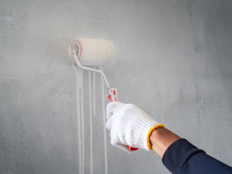 Sluit omhoog van arbeidershand gebruikend rol en borstel voor het schilderen van muur huis in doos op wit wordt geïsoleerd dat stock afbeeldingen