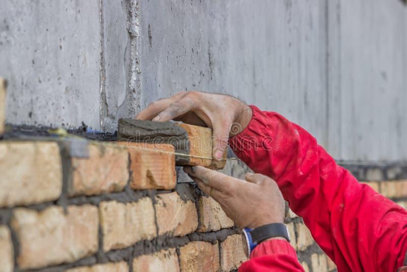 Sluit omhoog van arbeidershanden leggend baksteen stock afbeelding