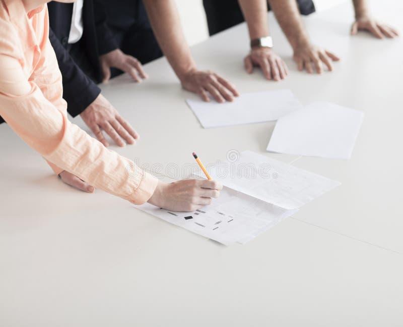 Sluit omhoog van armen en handen van bedrijfsmensen in het bureau die een commerciële vergadering hebben stock foto