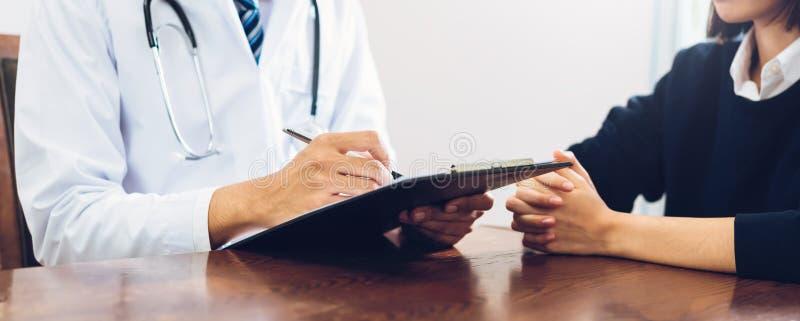 Sluit omhoog van arts en geduldige zittingshanden bij de lijst en het spreken over de voorwaarde van de patiënt royalty-vrije stock foto's