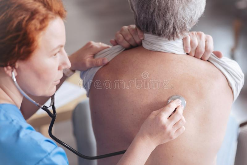Sluit omhoog van arts het luisteren terug van patiënt met stethoscoop stock foto's