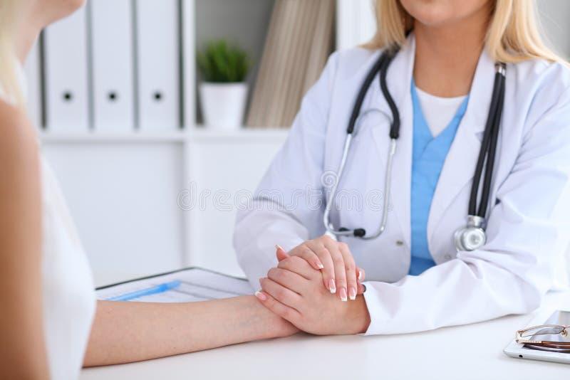 Sluit omhoog van artsenhanden geruststellend haar vrouwelijke patiënt stock foto's