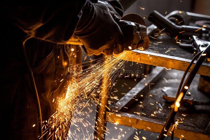 Sluit omhoog van auto mechanische handen die malende machine lassen Vonken van malende machine terwijl het snijden van autouitlaa royalty-vrije stock afbeelding