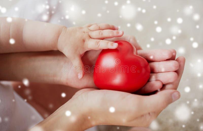 Sluit omhoog van baby en moederhanden met rood hart royalty-vrije stock foto's