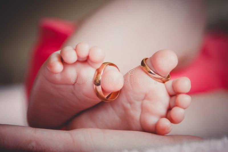 Sluit omhoog van baby` s voeten met trouwringen in moeder` s handen Pasgeboren Selectieve nadruk stock foto's