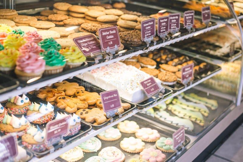 Sluit omhoog van bakkerijvitrine met koekjes en cupcakes stock afbeeldingen