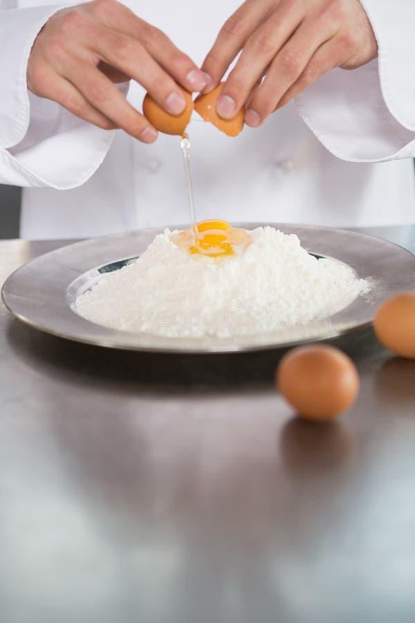 Sluit omhoog van bakkers brekende eieren in bloem royalty-vrije stock foto's