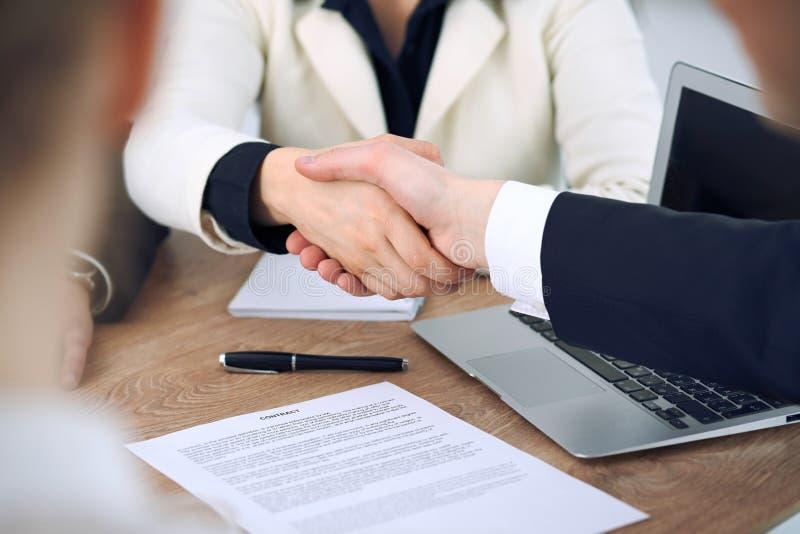 Sluit omhoog van bedrijfsmensen die handen schudden bij vergadering of onderhandeling in het bureau De partners zijn tevreden omd stock afbeeldingen