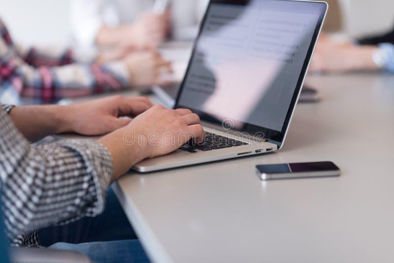 Sluit omhoog van bedrijfsmensenhanden typend op laptop met team op mee stock fotografie
