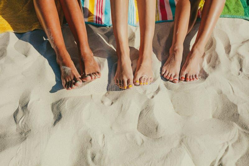 Sluit omhoog van benen van drie vrouwen bij het strand stock foto's