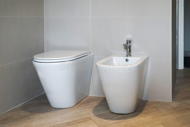Sluit omhoog van Bidet en WC in de badkamers stock afbeeldingen