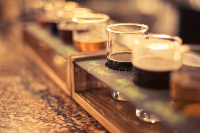 Sluit omhoog van biervluchten op de bovenkant van de granietbar met selectieve nadruk stock foto