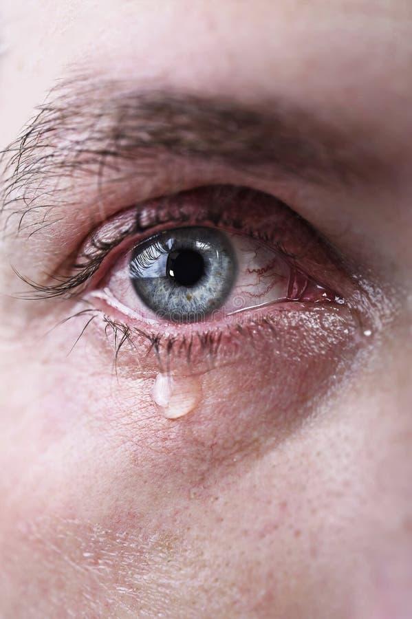 Sluit omhoog van blauw oog van de mens die in scheuren droevig en volledig van pijn in depressie schreeuwen stock afbeelding