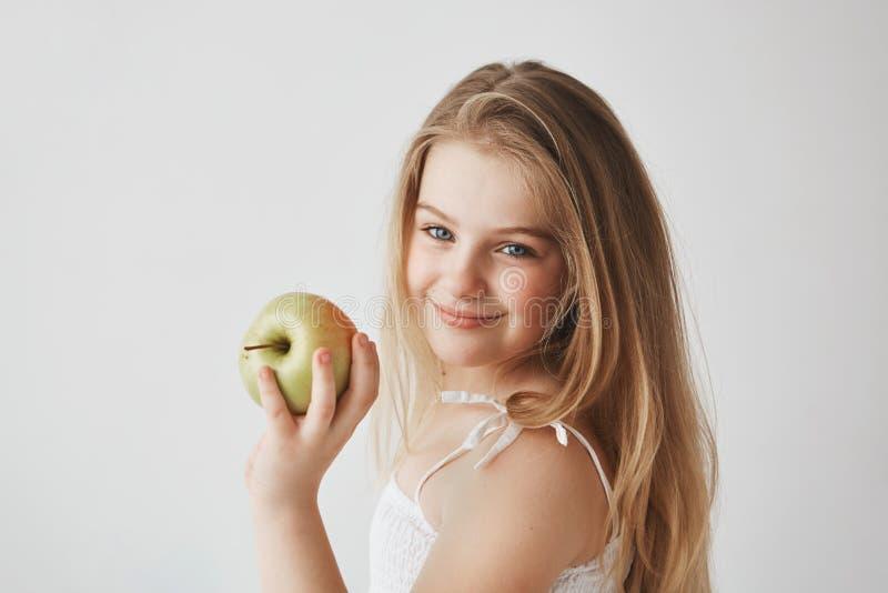 Sluit omhoog van blij klein licht-haired meisje die met blauwe ogen in de witte in hand appel van de kledingsholding, brightfully royalty-vrije stock foto's