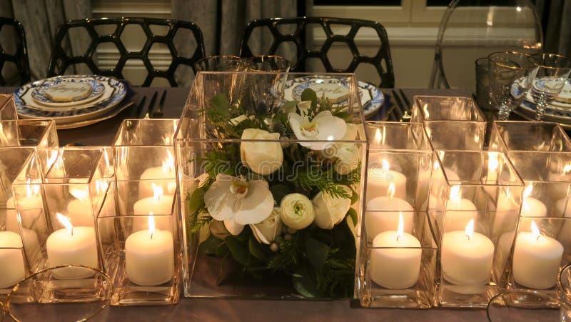 Sluit omhoog van bloemdecor en kaarsen op de dinerlijst royalty-vrije stock afbeelding