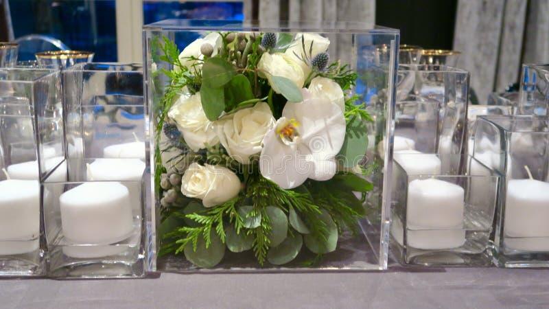 Sluit omhoog van bloemdecor en kaarsen op de dinerlijst stock afbeeldingen