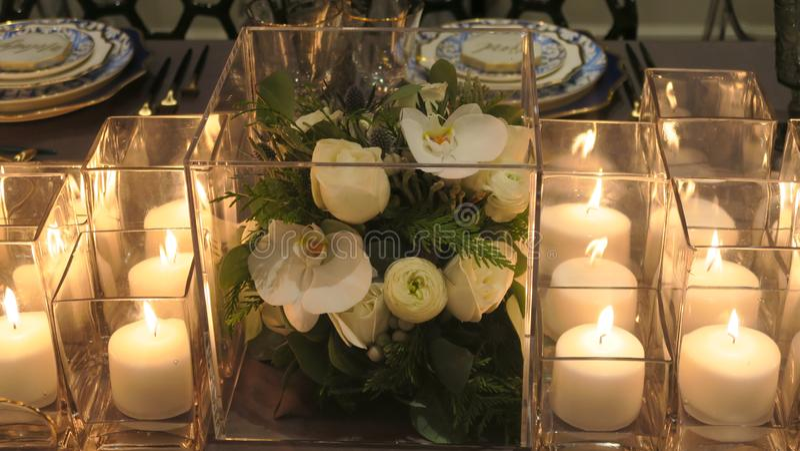Sluit omhoog van bloemen, kaarsen op de dinerlijst stock fotografie