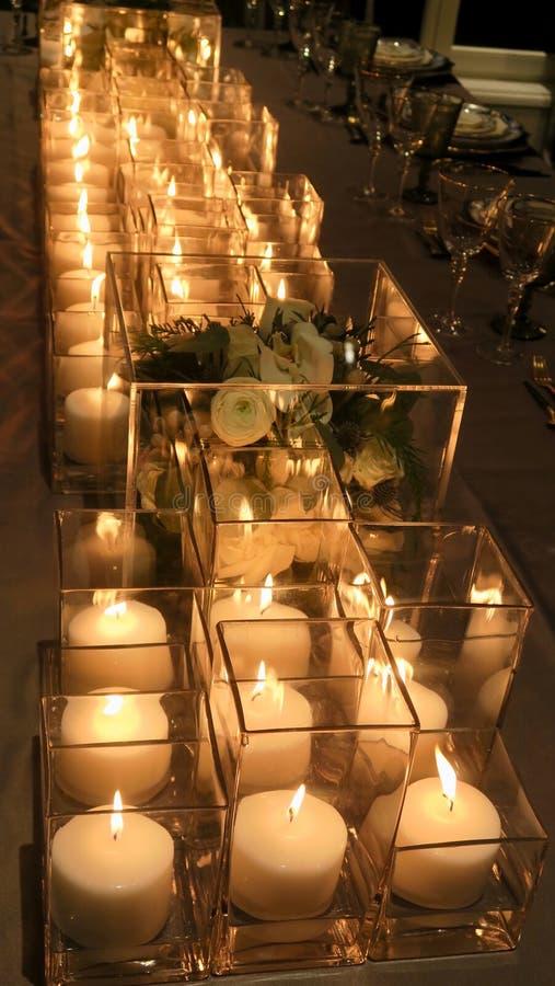 Sluit omhoog van bloemen, kaarsen op de dinerlijst stock foto's