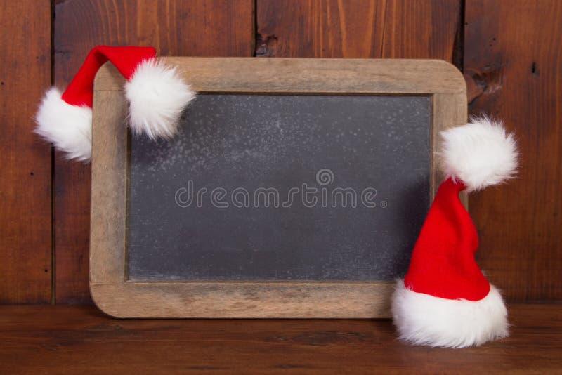 Sluit omhoog van bord met Kerstmanhoed voor een Kerstmisgroet c stock fotografie