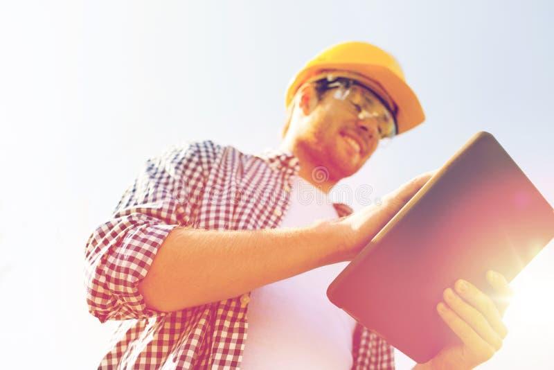 Sluit omhoog van bouwer in bouwvakker met tabletpc stock foto