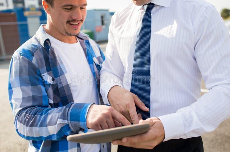 Sluit omhoog van bouwer en zakenman met tabletpc stock afbeeldingen