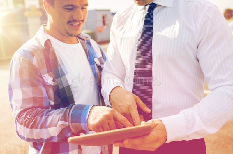 Sluit omhoog van bouwer en zakenman met tabletpc stock foto's